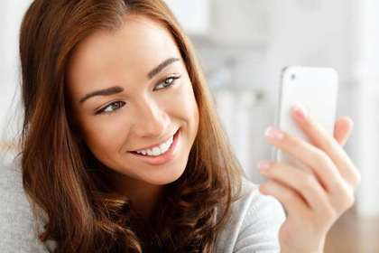 スマホを見て微笑む女性