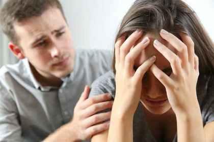頭を抱える女性と慰める男性