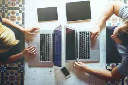 向かい合ってパソコンを使う二人