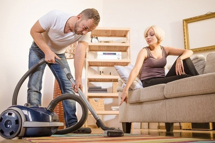 女性に指示されて掃除機を使う男性