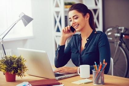 パソコンを見ながら電話する女性画像