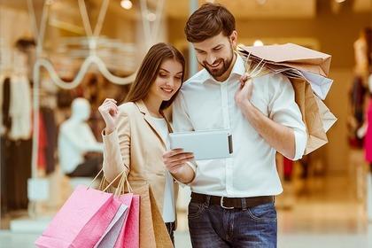 買い物袋を下げて携帯をみている女性と男性