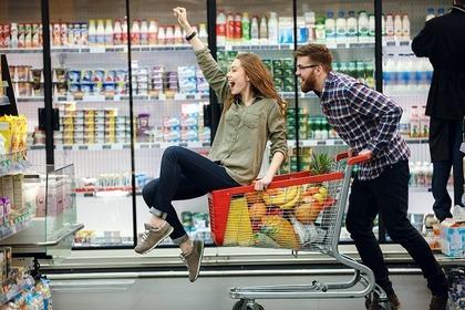 ショッピングカートに乗っている女性を引いてる男性