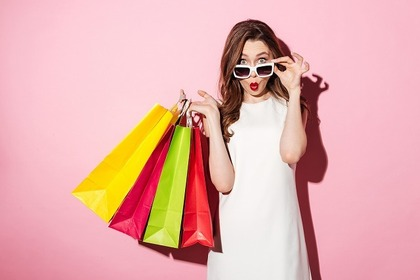 サングラスをかけて買い物袋を持っている女性