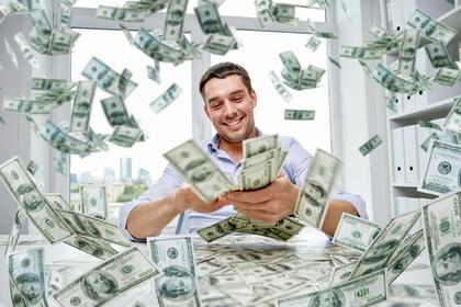舞うお金の中で喜ぶ男性