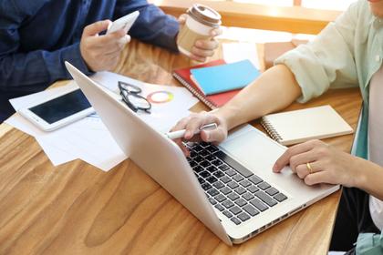 パソコンを見て商談する男性二人