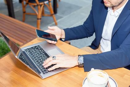 携帯とパソコンで連絡を取るスーツ姿の男性画像