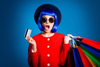 カードとカラフルなショッピングバッグを持った女性