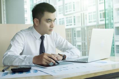 パソコンを見ながらメモを取る男性