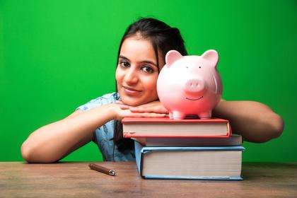 本と貯金箱を前にする女性