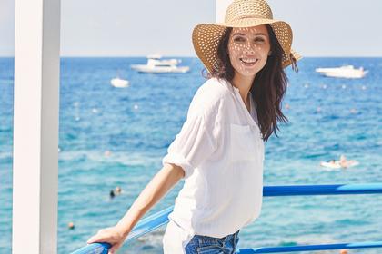 海の近くで麦わら帽子をかぶってほほ笑む女性